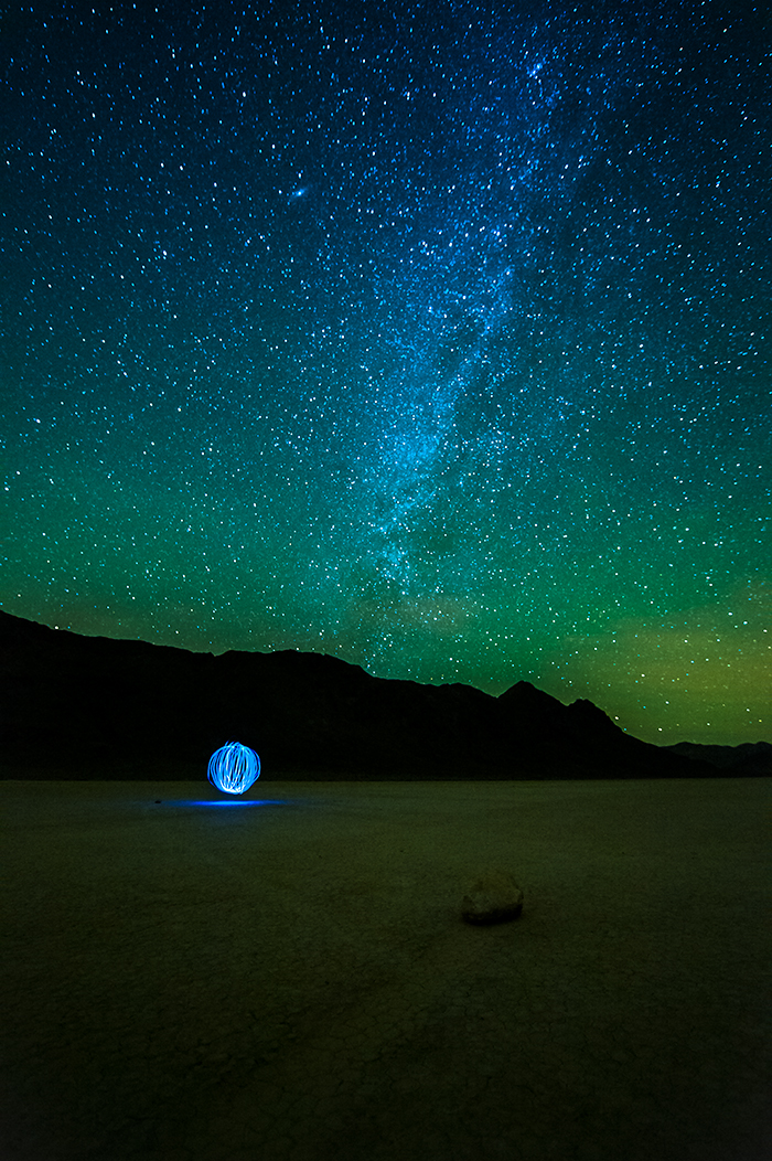 Night photo Racetrack Playa dry lake bed with prominent view of milky way and a flashlight pattern that appears as an orb in the distance. Death Valley