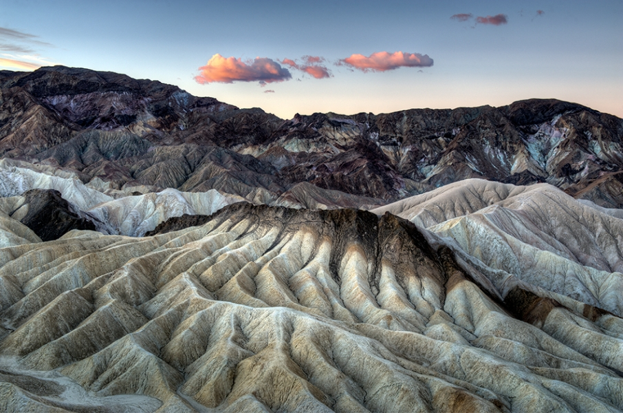 Zabriskie Point overlook in Death Valley at sunrise with trellis drainage and 2 clouds in the center.
