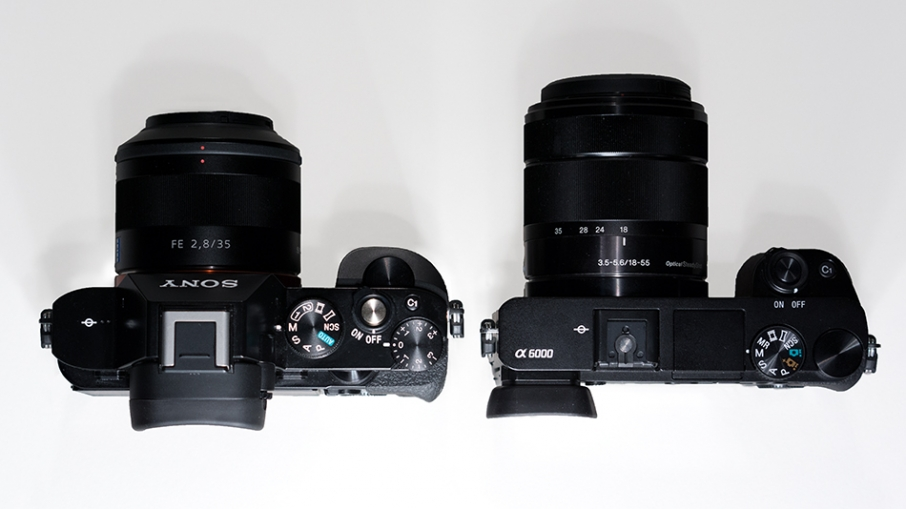 A7R (left) and the A6000. On the slimmer A6000, note the left justified viewfinder, pop up flash, no compensation dial, no front dial, no quick access to memory settings 1&2, no hot shoe cover.